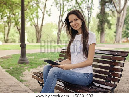 Beautiful caucasian girl reading a e-book in the park and smiling