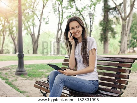Beautiful caucasian girl talking on the phone with a e-book on her hand in the park