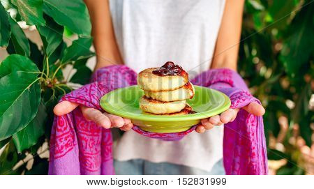 Sweet ricotta pancakes with cherry jam on a violet indian napkin in the woman's hands.