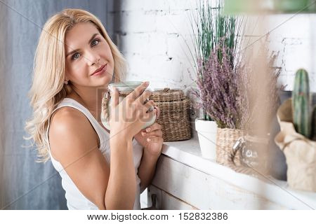 Nice thing. Sweet blond woman standing near decorated shelf and holding designed shelf.