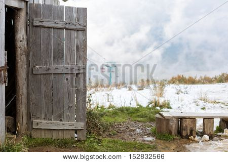Open wooden door of the old barn on the background of the chair lift at a ski resort in winter.