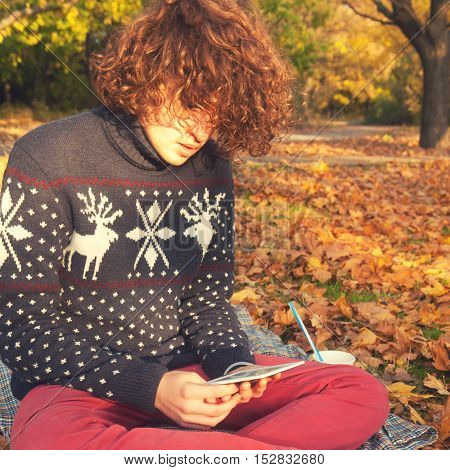 Young man dressed in knit sweater with deers and red jeans, have a leisure sitting in autumn park and reading the electronic book
