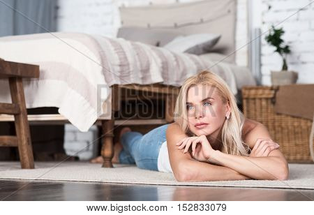 Thinking about life. Nice blond haired woman on floor in good decorated bedroom with hand at chin.