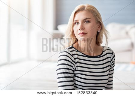 Feeling confident. Good-looking serious blond woman on background of white decorated room.