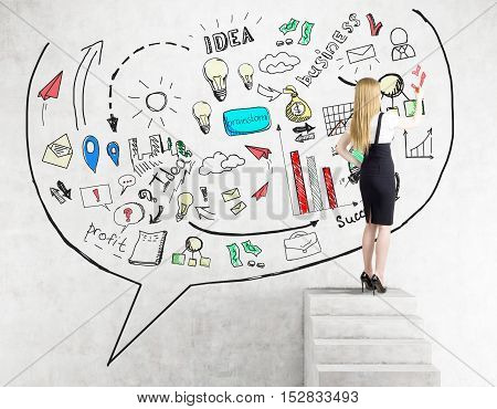 Rear view of blond woman drawing business idea sketch on concrete wall while standing on stairs. Concept of idea development