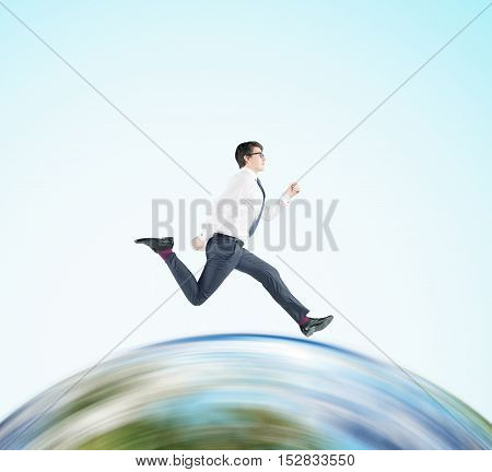Side view of businessman in glasses running on huge globe. Concept of international business. Mock up.