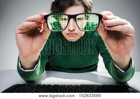 Close up of nerdy guy with keyboard who has taken off his glasses and looking at green data flow in them. Concept of IT work