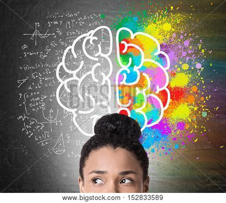Close up of African American woman's head with large brain drawing. One hemisphere is colored. The second is surrounded by formulas. Concept of logic and creativity