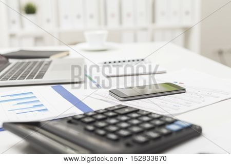 Close up of office employee's desk with calculator laptop smartphone and cup of coffee in the background. Concept of office life