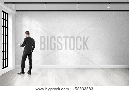 Rear view of businessman with cell phone who is calling the police because his office was robbed. Concept of crime. 3d rendering. Mock up