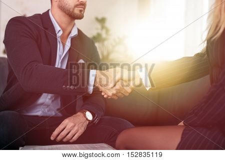 Businessman handshake with businesswoman in office closeup in sunset