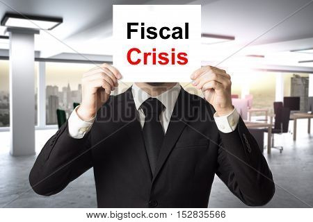businessman in black suit hiding face behind sign fiscal crisis