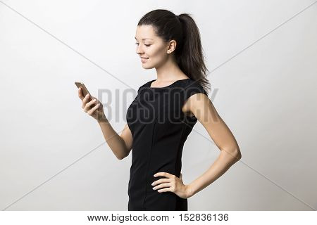 Side view of young lady in beautiful black dress looking at her cell phone screen and standing against white background. Mock up
