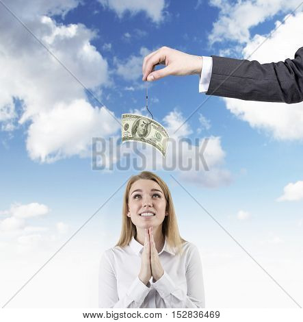 Hoping woman is standing against sky background. Large man's hand with dollar note on the hook is above her head. Concept of fraud