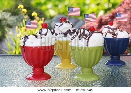 Ice cream sundaes decorated with American flags for July fourth. Focus on the front two bowls.