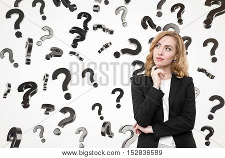 Beautiful businesswoman with red hair is standing against white background. Question marks are falling from the sky. Concept of looking for solution