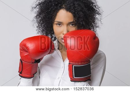 Serious African American Girl With Red Boxing Gloves Wearing Formal Clothes And Looking At The Viewe