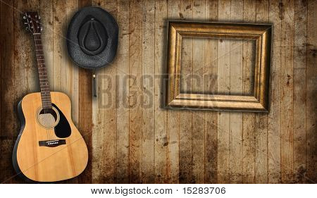 Cowboy hat, guitar and empty picture frame, against an old barn background.