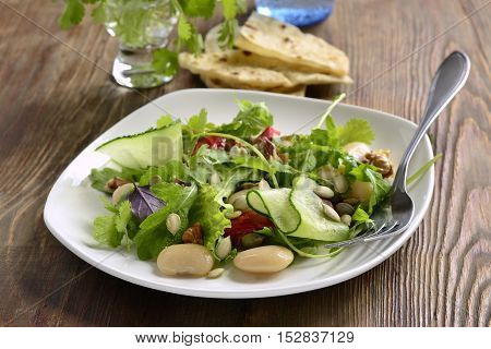 Mixed salad with white beans greens cucumbers and sweet peppers