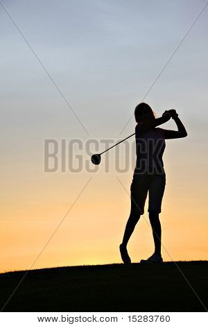Lady golfer swinging her driver at sunrise.