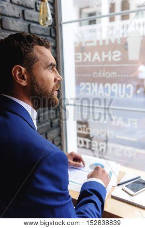 elegant freelancer on his workspace in cafe looking thru the window