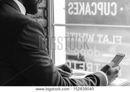 elegant man holding smartphone while sitting at the cafeteria, black and white