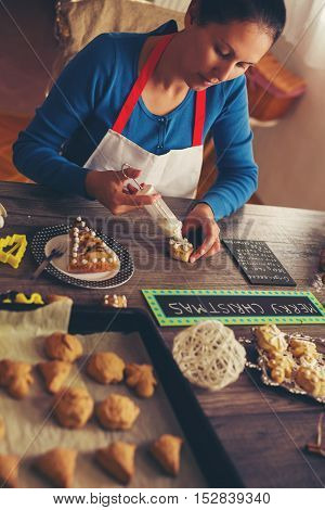 Woman decorating gingerbread cookies on wooden background