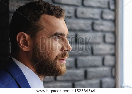 side view of bearded businessman's face sitting indoors with copy space