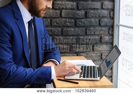 workplace of a smart handsome man sitting in a cafe with laptop