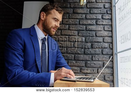 side view of a handsome freelancer sitting against the black brick wall with copy space