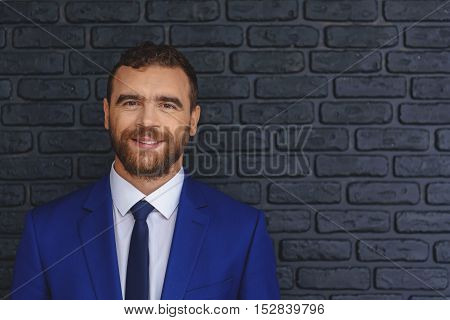 smiling cheerful man in costume standing in front of a black wall with copy space, ideas and success concept
