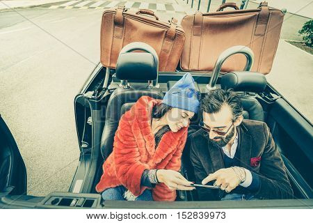 Happy couple having fun with satnav at car travel - Hipster guy having fun with fashion girlfriend at road trip - Love relationship concept with young people on tour together - Soft retro lomo filter