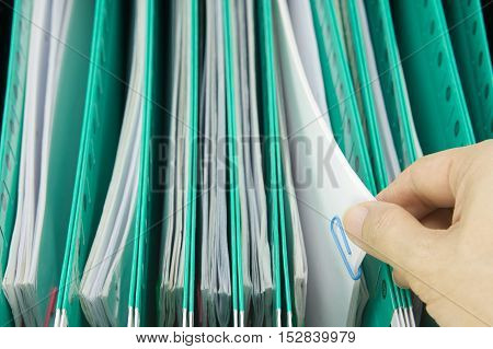 Man Pick Paperwork From Green Suspension Folder Hang In Cabinet