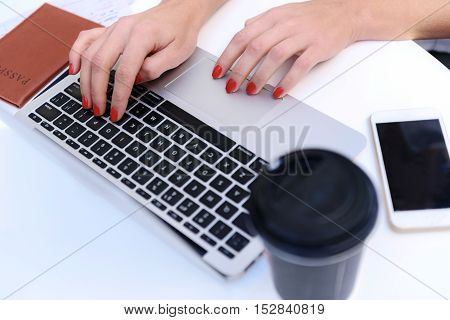 hands of a woman with a manicure typing on a keyboard, while passport and coffee on the table