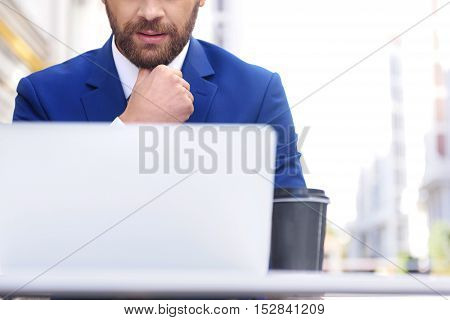 front view of a confident man in costume sitting in front of a laptop