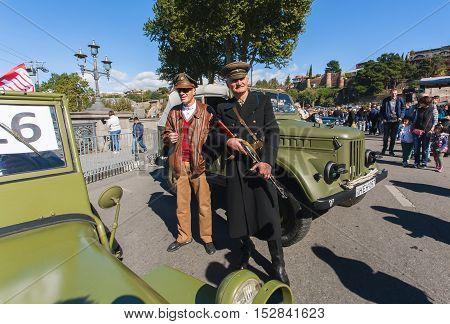 TBILISI, GEORGIA - OCT 16, 2016: Seniors in military uniform standing near retro cars of Second World War on show of Tbilisoba on October 16, 2016. Tbilisoba is festival in Tbilisi from 1979