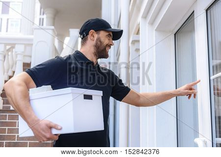 man from delivery service with a box ringing the door bell, side view