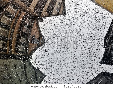 The surface of the car with reflections of old houses in rain drops.