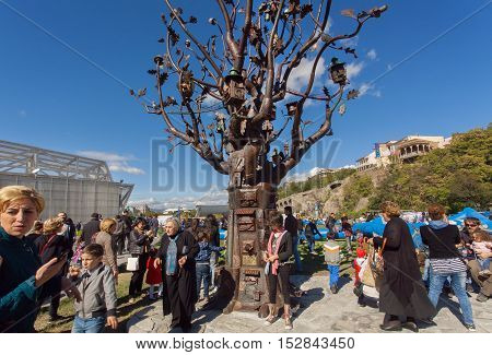 TBILISI, GEORGIA - OCT 16, 2016: Many people with families walking in Rike park with metal Tree of Life during city festival Tbilisoba on October 16, 2016. Tbilisi has a population of 1.5 million people