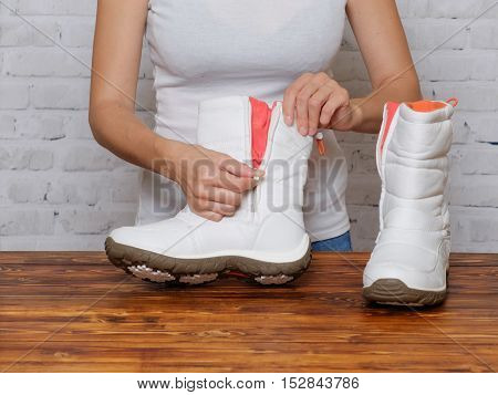 Woman unzips the zipper on the new boots
