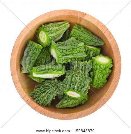 top view of bitter melon in wooden bowl isolated on white