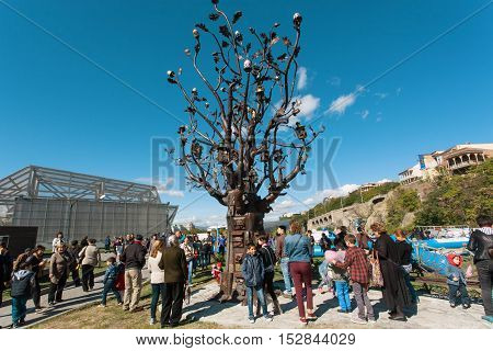 TBILISI, GEORGIA - OCT 16, 2016: Green park and people with children watching iron sculpture Tree at festival Tbilisoba on October 16, 2016. Tbilisoba is traditional festival in capital of Georgia from 197
