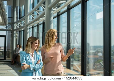 Two business woman looking through the office window.