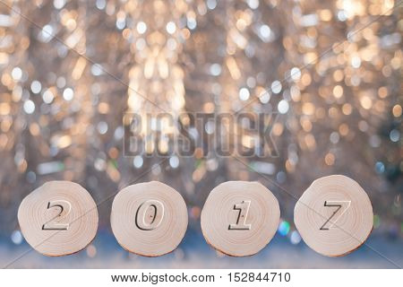 Four alder saw cuts and convex date 2017 on beautiful Christmas golden bokeh background. New year or Christmas background.