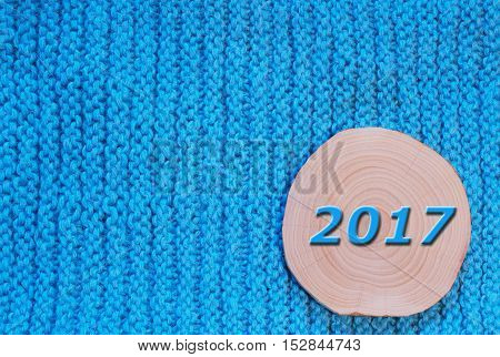Round saw cut alder and blue date 2017 on blue knitted fabric background. New Year`s and Christmas background.