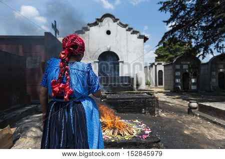 Chichicastenango Guatemala - April 24 2014: Maya woman performing a traditional mayan ritual in the cemetery of the town of Chichicastenango in Guatemala