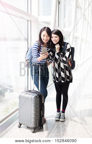 two woman use smart phone in airport in hongkong asian