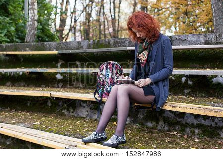 Ginger woman sitting on the bench in the autumn park with a tablet