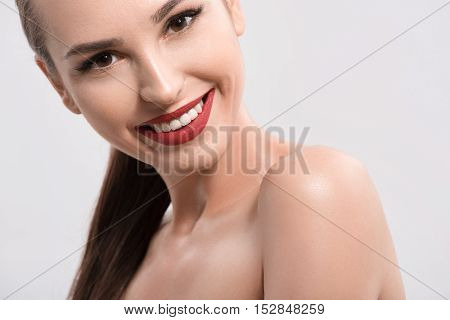 Happy young woman has healthy skin. She is standing with naked shoulders and smiling. Isolated