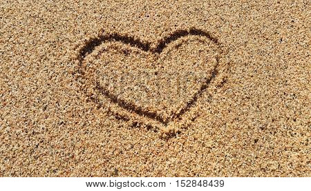Abstract love symbol drawing on sandy sand beach background